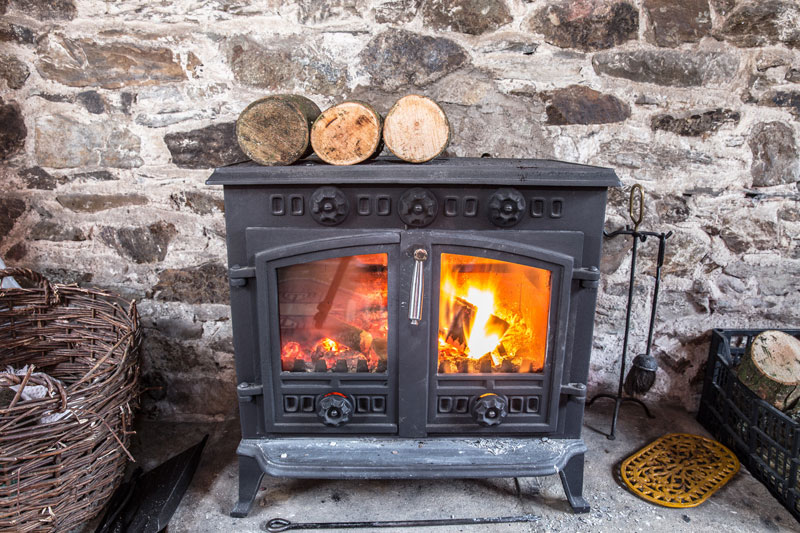 vintage black wood stove with blazing fire